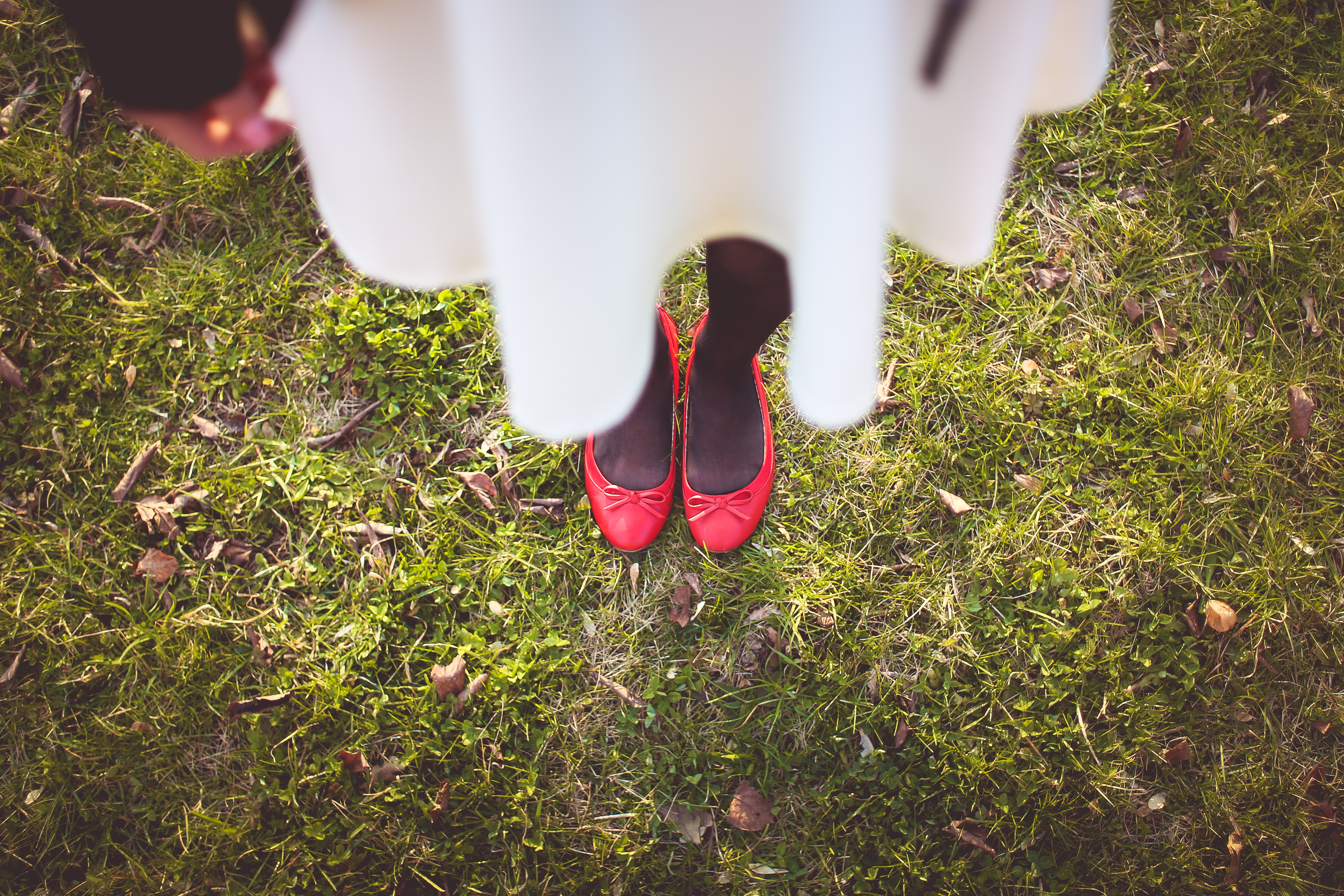 Mädchen in weißem Kleid und roten Ballerina-Schuhen