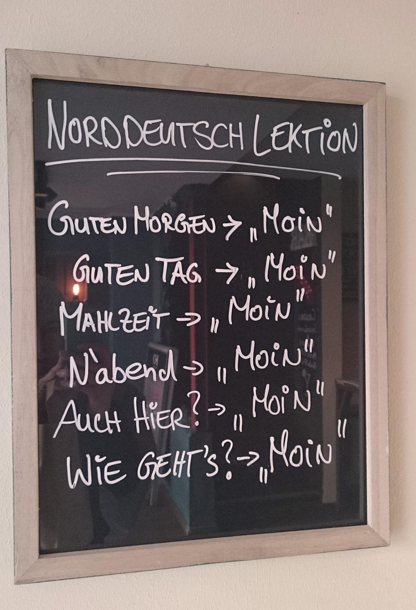 Norddeutsche Sprachlektüre im Bilderrahmen beim Bremer Café Brill No. 6: Moin geht immer.