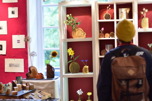 Eine Besucherin staunt über Bilder, Holzvasen und Kerzen auf der La Weser.
